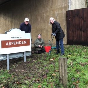 People planting bulbs next to village sign